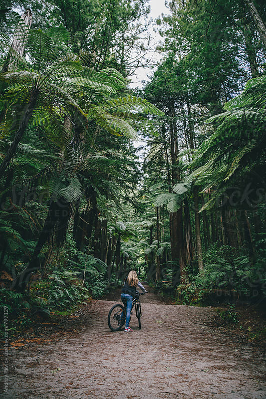 Woman riding on a bicycle in the Whakarewarewa forest by Andrey Pavlov for Stocksy United