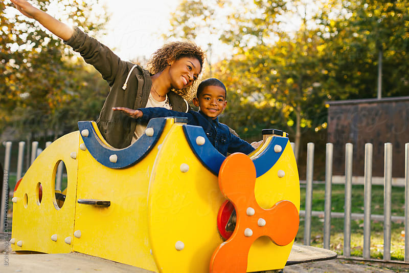 Mother and her son having fun on a playground in autumn. by BONNINSTUDIO for Stocksy United