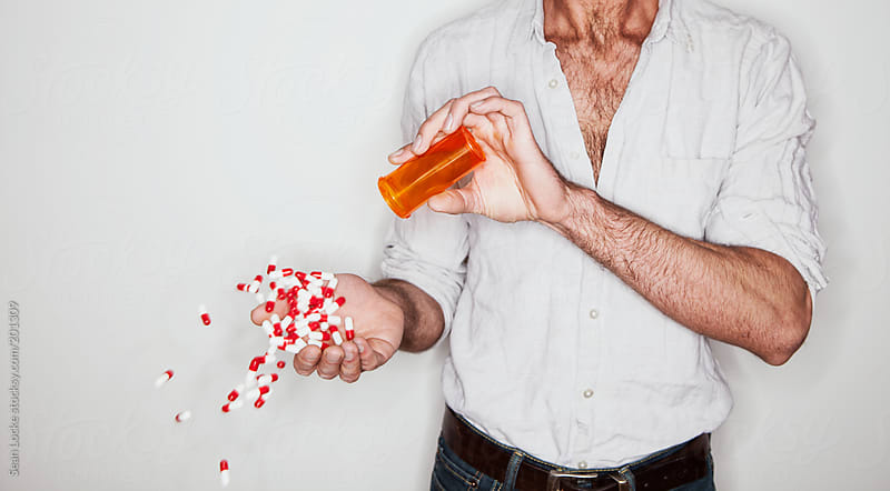 Portraits: Man Dumping Capsules Out Into Hand by Sean Locke for Stocksy United