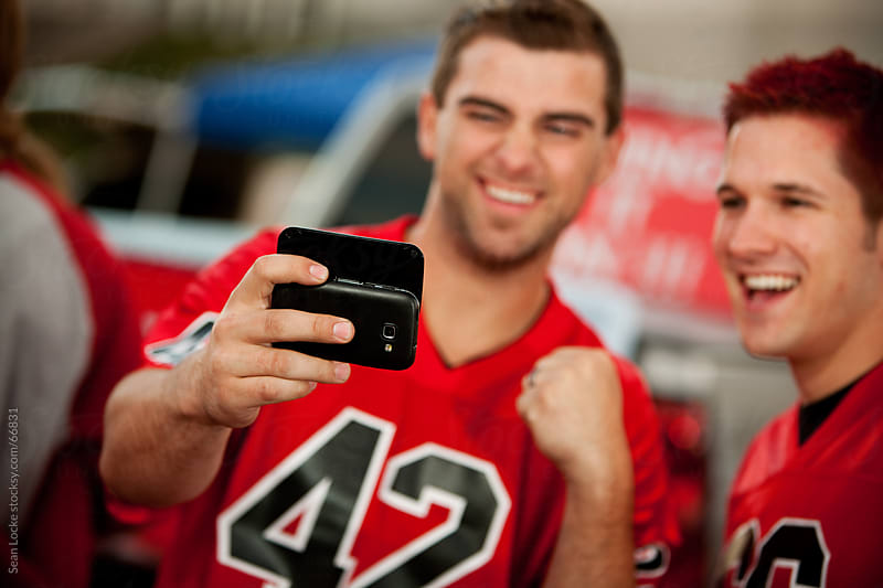 Tailgating: Guys Check Out Sports Information on Cell Phone by Sean Locke for Stocksy United