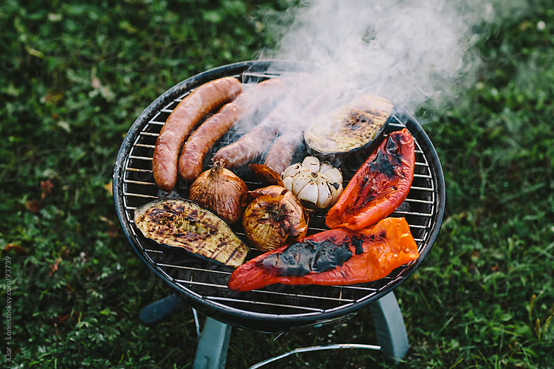 Sausages and vegetables roasting over barbecue by Lior + Lone for Stocksy United