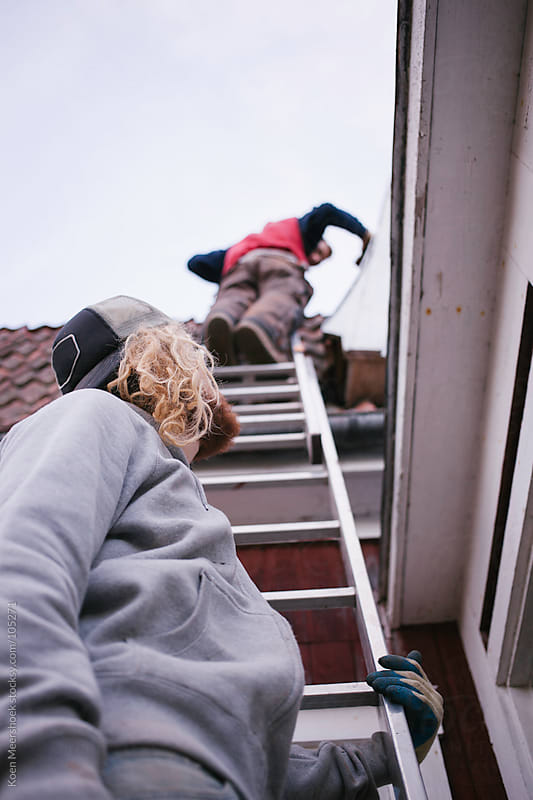Two man standing on a ladder working on the roof. by Koen Meershoek for Stocksy United