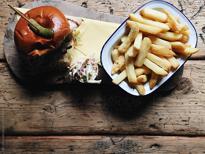 Chicken burger in brioche bun with fries by Suzi Marshall for Stocksy United