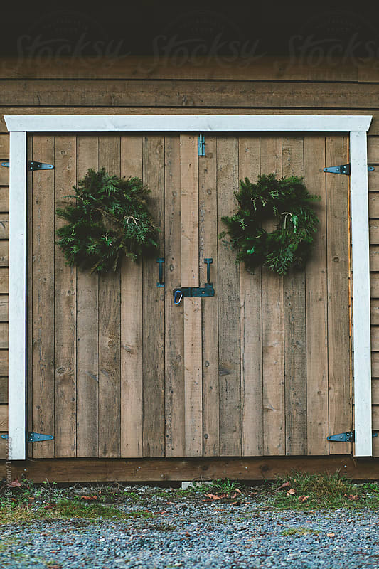 Woodshed doors are decorated with wreaths. by Cherish Bryck for Stocksy United