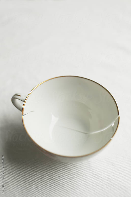 broken, cracked teacup on a table by Kelly Knox for Stocksy United
