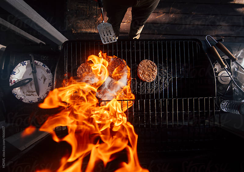 The fire on the grill roars as the burgers cook  by HOWL for Stocksy United