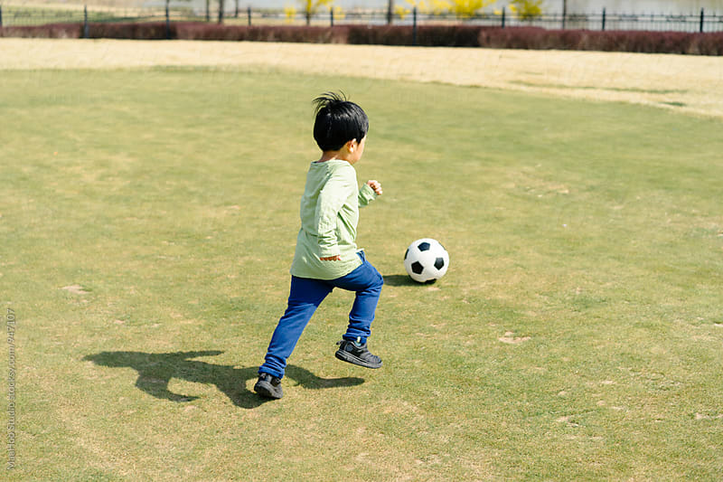 Boy playing football on grass by Maa Hoo for Stocksy United