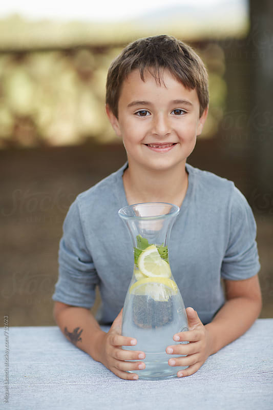 Smiling kid holding a water jar with lemon on a table by Miquel Llonch for Stocksy United
