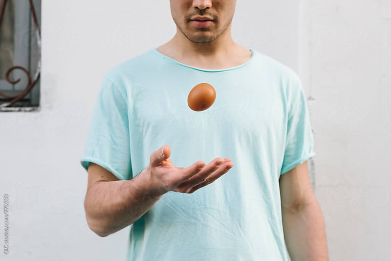 Man playing with an egg by Simone Becchetti for Stocksy United