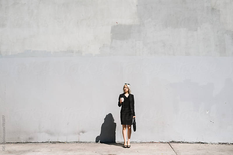 Cool businesswoman against a big wall by Simone Becchetti for Stocksy United