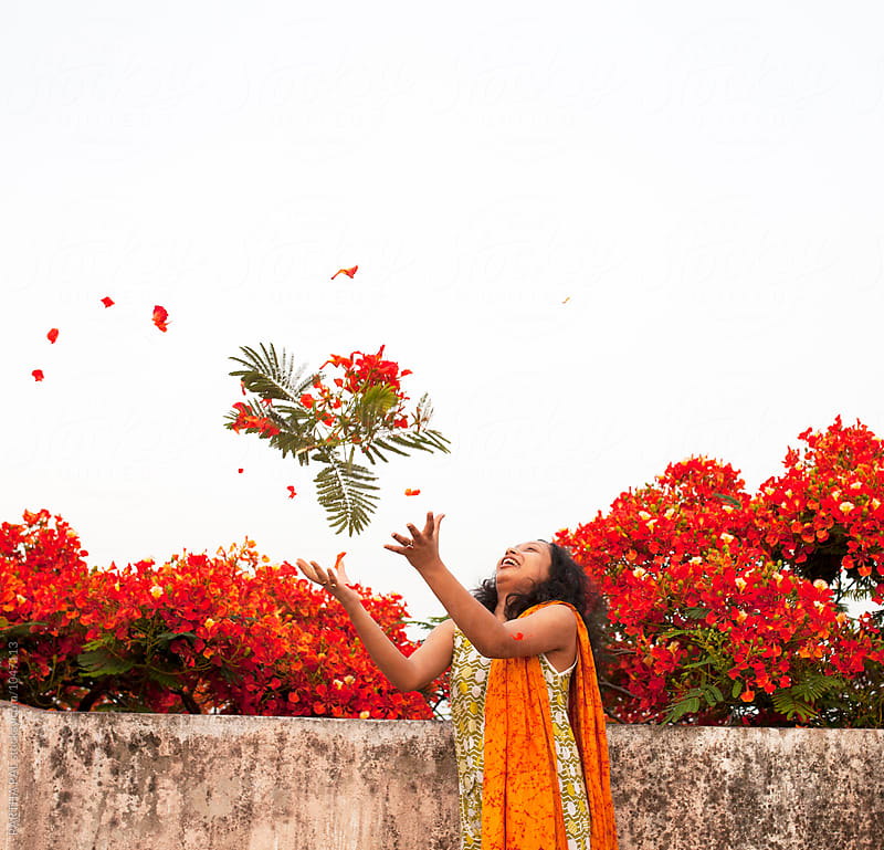 Happy Indian Woman trying to catch red flowers with branch by PARTHA PAL for Stocksy United