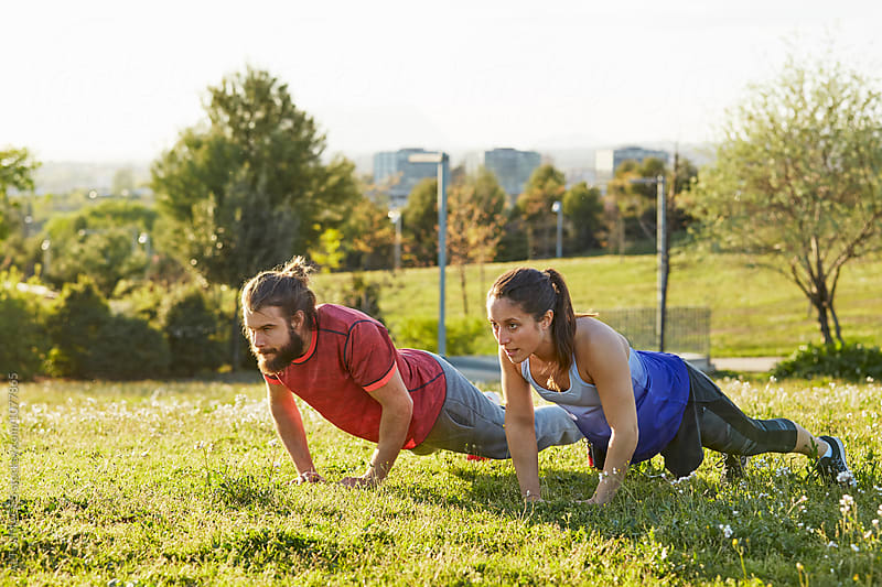 Determined Athletes Doing Push-Ups In Park by ALTO IMAGES for Stocksy United