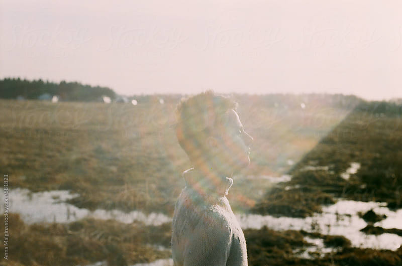 A film portrait of a young beautiful men in winter wth a sunshine on his face by Anna Malgina for Stocksy United