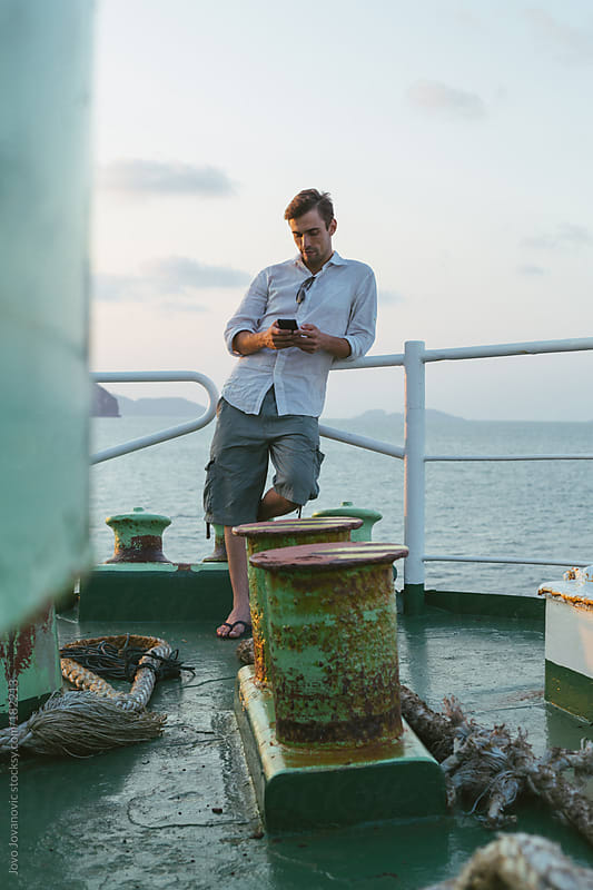 Man looking at his mobile phone by Jovo Jovanovic for Stocksy United