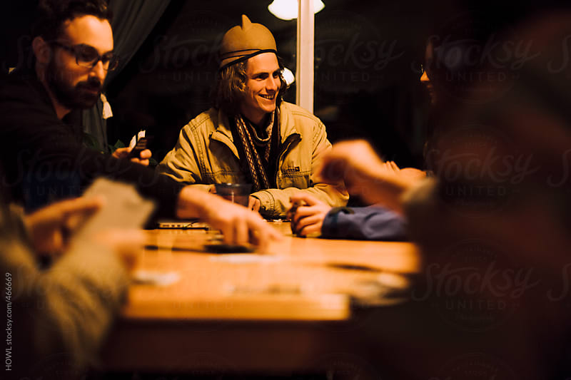 a group of friends gather at the table for a game by HOWL for Stocksy United