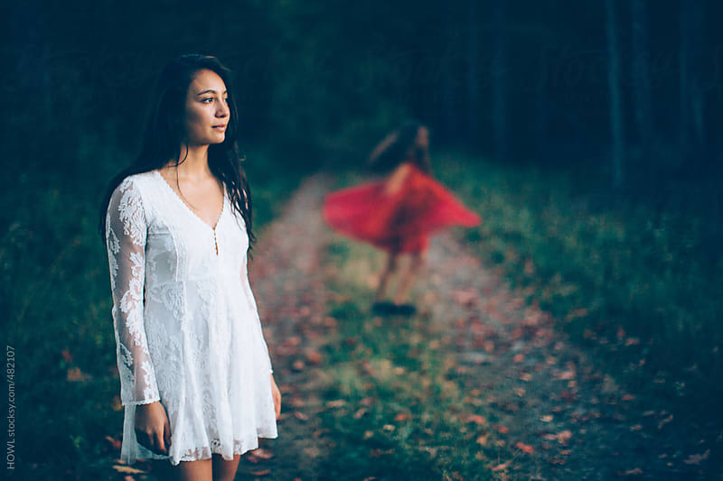 Brunette woman in white lace dress looks into the forest  by HOWL for Stocksy United