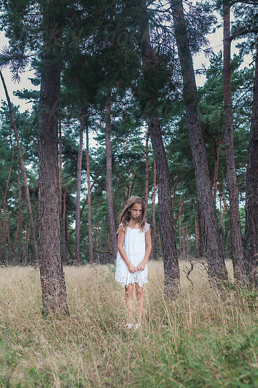 Little girl in a white dress standing in the woods by Cindy Prins for Stocksy United