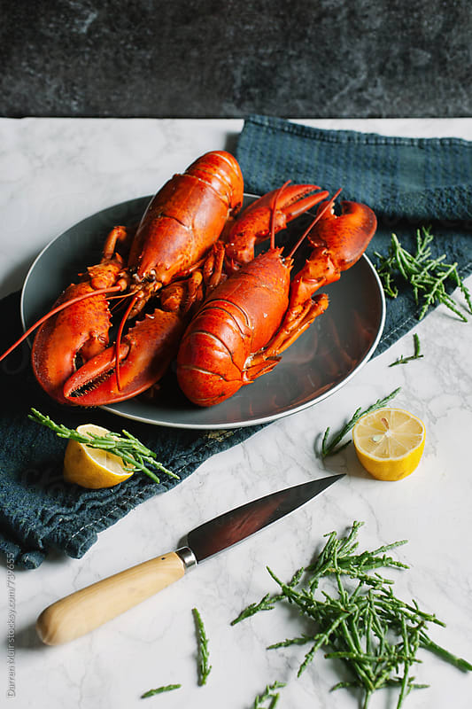 Two cooked lobsters on a plate on a table with samphire and lemon. by Darren Muir for Stocksy United