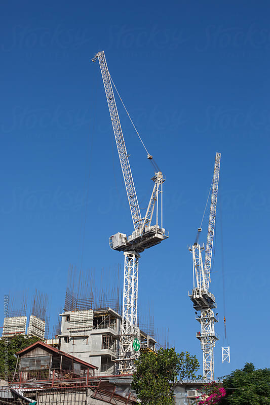 Two cranes sit idly during construction break in the city by Lawrence del Mundo for Stocksy United