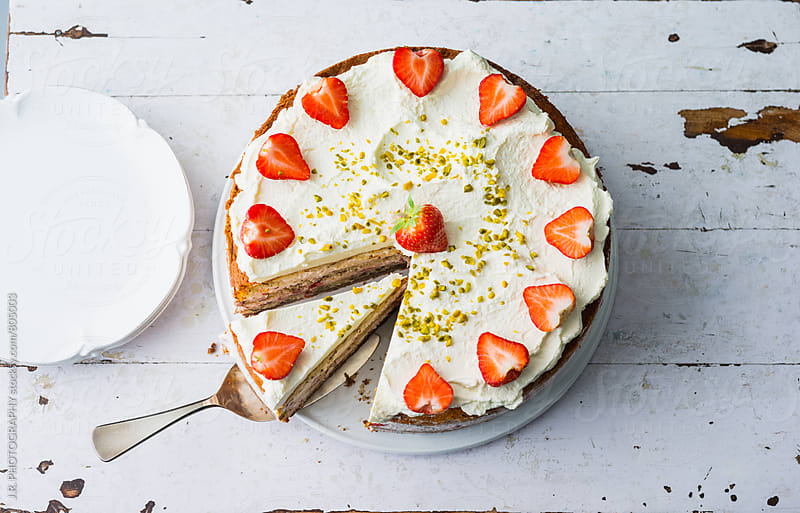 Preparing strawberry cream cake by J.R. PHOTOGRAPHY for Stocksy United
