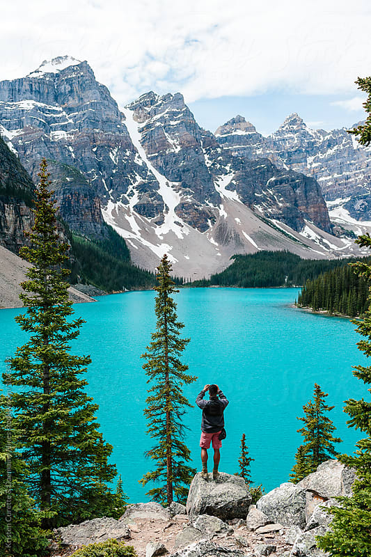 A man standing on a rock taking a photo of Moraine Lake & the mountains by Kristen Curette Hines for Stocksy United