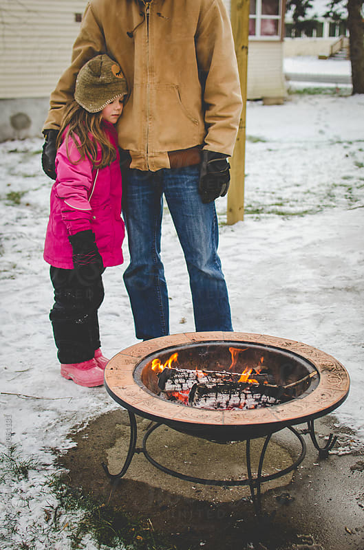 Father and daughter holding each other beside fire pit outside during winter by Lindsay Crandall for Stocksy United