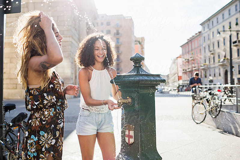 Two girls refresh themselves at the fountain on a hot day by michela ravasio for Stocksy United