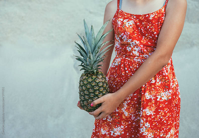 Girl in a red dress with an organic pineapple by Carolyn Lagattuta for Stocksy United