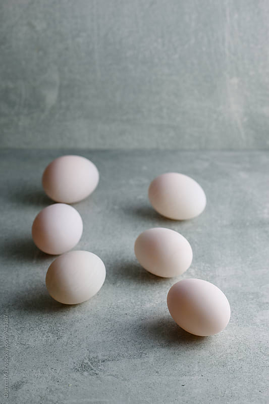 Six duck eggs in concrete background. by Darren Muir for Stocksy United