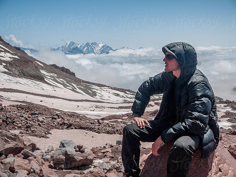 Young hiker sitting on a stone with inversion in the background by Martin Matej for Stocksy United