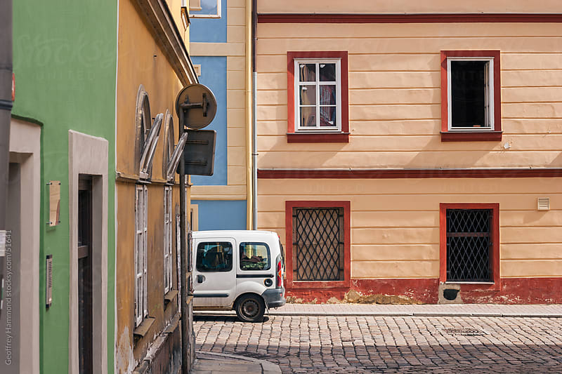 A Small Delivery Vehicle Parked Among Colorful Buildings in Cheb by Geoffrey Hammond for Stocksy United