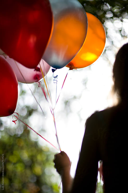 girl holding balloons by Lee Avison for Stocksy United