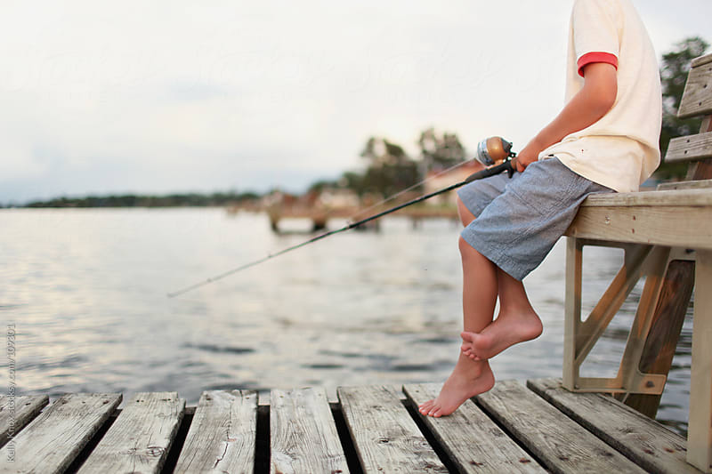 boy fishes from a pier by Kelly Knox for Stocksy United