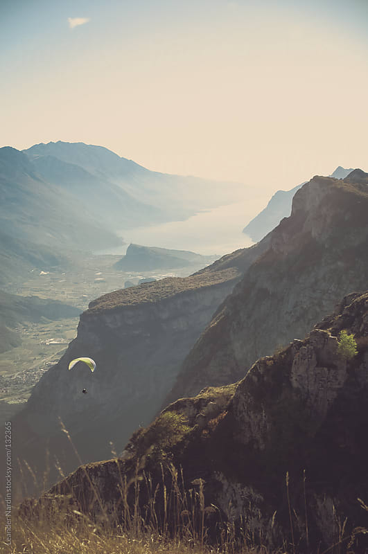 paraglider flying in the mountains with autumnal sunet light by Leander Nardin for Stocksy United