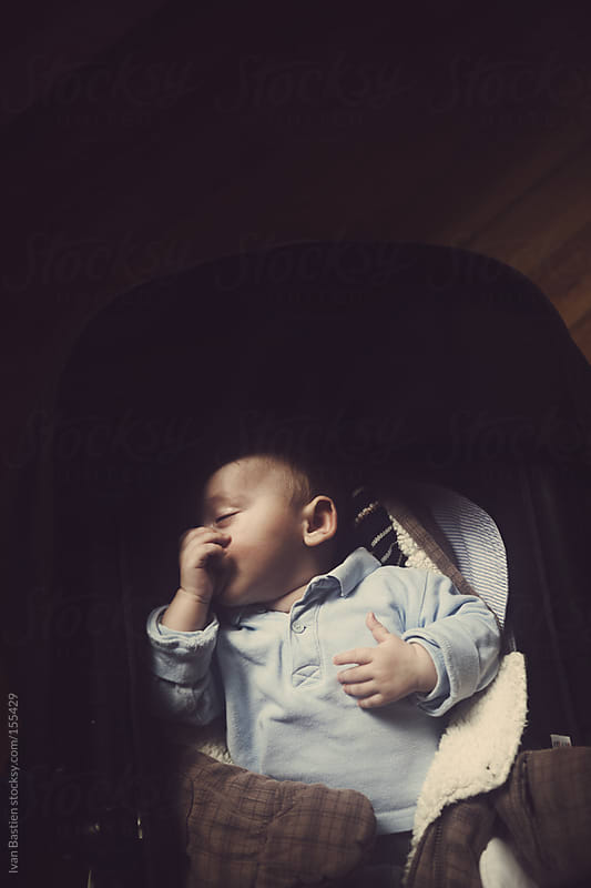 Baby boy sucking his thumb in a stroller by Ivan Bastien for Stocksy United