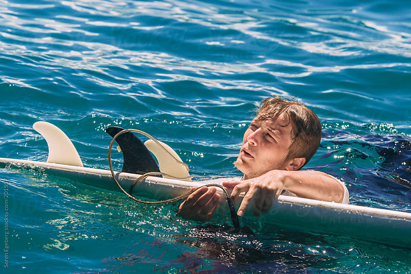 Young blond surfer in the blue sea with his surfboard in summer by Soren Egeberg for Stocksy United