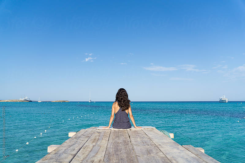 Young woman sitting on a pier by ACALU Studio for Stocksy United