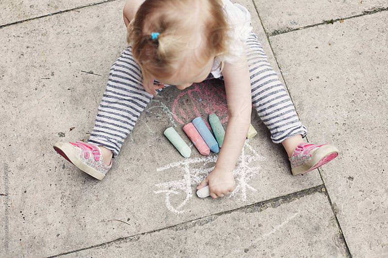 Child drawing with chalk on the floor by sally anscombe for Stocksy United