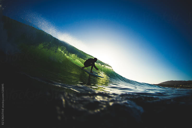 Backlit surfer dropping into a wave. by RZ CREATIVE for Stocksy United