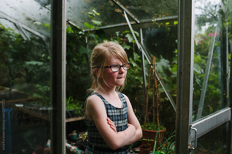 Young girl stands thoughtfully at the entrance to a garden glasshouse. by Julia Forsman for Stocksy United