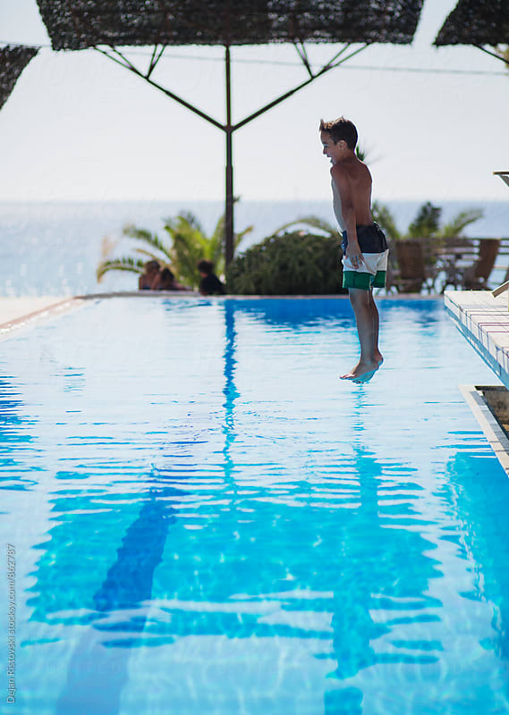 Boy jumping into a swimming pool. by Dejan Ristovski for Stocksy United