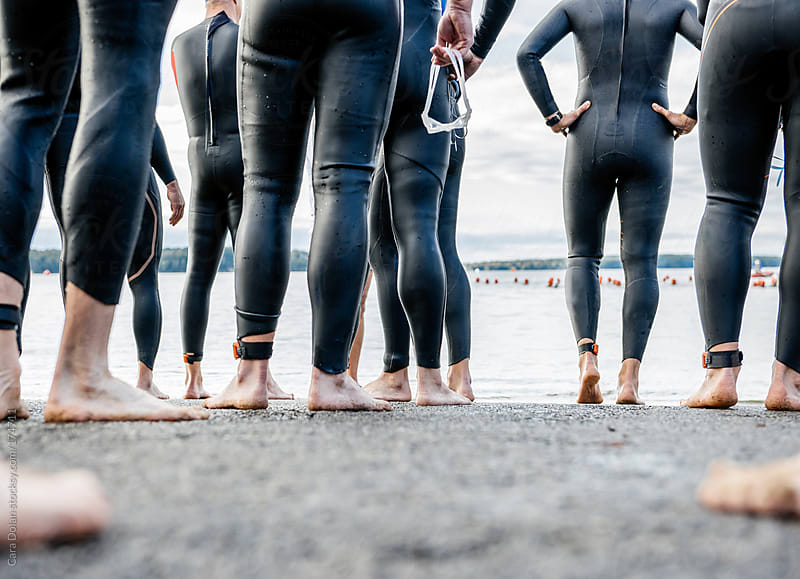 Male athletes in wet suits at the start line of a triathlon by Cara Dolan for Stocksy United