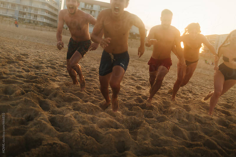A group of friends run into the ocean  by HOWL for Stocksy United