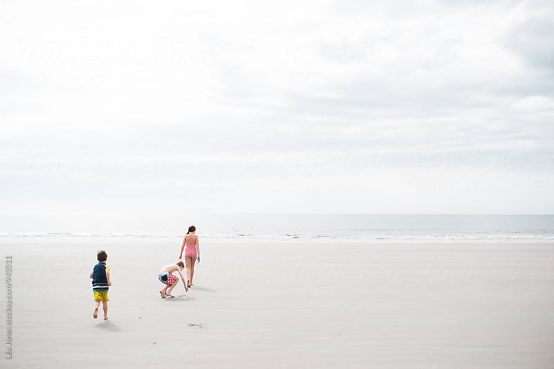 three kids playing on the beach by Léa Jones for Stocksy United