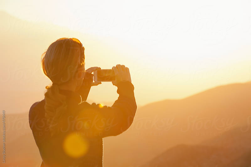 Young female taking photo of sunset from mountain viewpoint. by Linzy Slusher for Stocksy United
