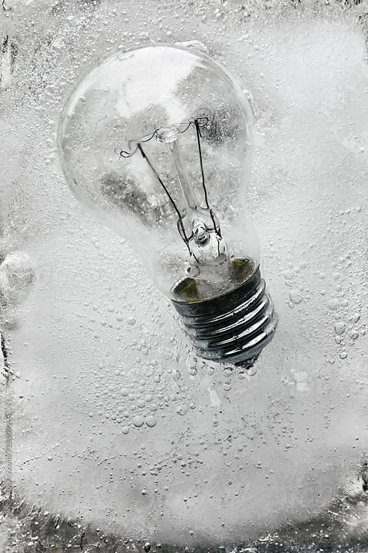 frozen bulb in a block of ice by Igor Madjinca for Stocksy United