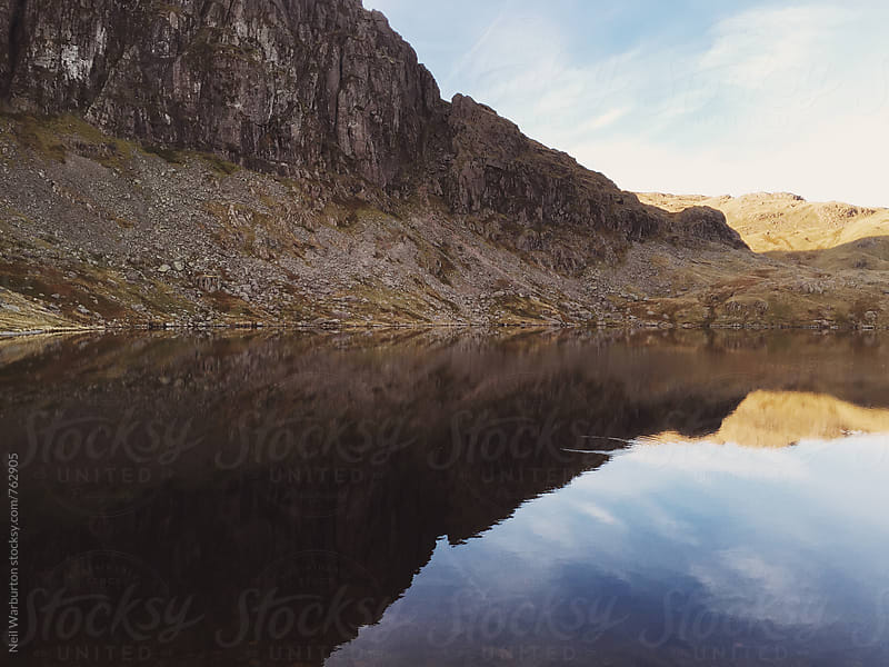 Crag face reflected in mountain lake by Neil Warburton for Stocksy United
