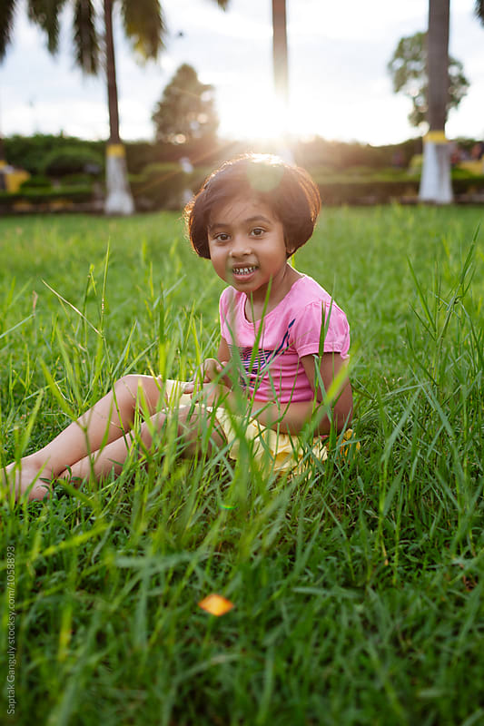 Smiling portrait of little girl sitting on the grass by Saptak Ganguly for Stocksy United