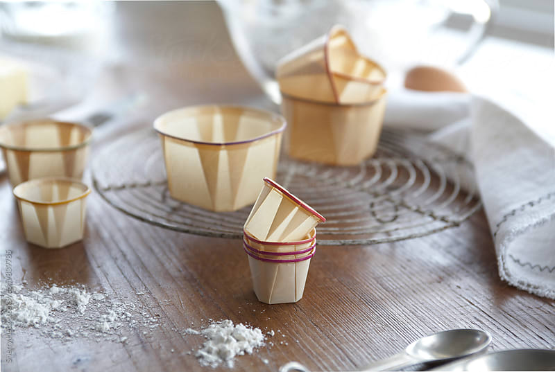 Waxed paper baking cups on wood surface with white linen napkins by Sherry Heck for Stocksy United