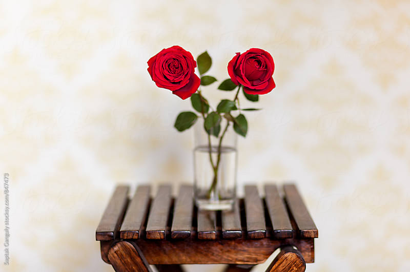 Two red roses in a glass container on a wooden stool by Saptak Ganguly for Stocksy United